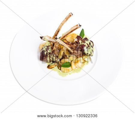 Grilled lamb racks with green butter and baked potatoes. Isolated on a white background.