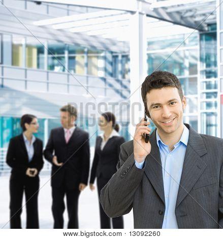 Portrait of happy businessman talking on mobile in office lounge.