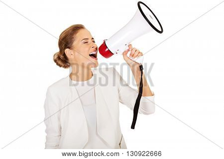 Beautiful businesswoman screaming through megaphone