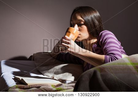 Young woman relaxing in her bed before sleep. She is reading a book and drinking tea.