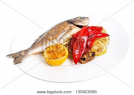 Grilled seabass with delicious vegetables on plate. Isolated on a white background.