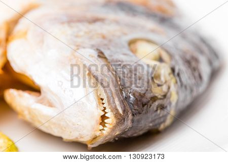 Closeup of grilled seabass head with teeth. Macro. Photo can be used as a whole background.