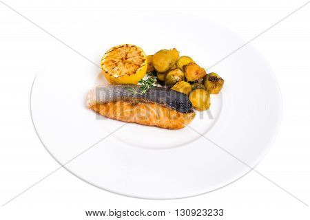 Grilled salmon fillet with brussel sprouts and sliced lemon. Isolated on a white background.