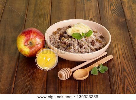 Healthy breakfast - a bowl of oatmeal with raisins and a banana, honey and apple on background of dark wood.