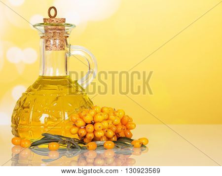 Buckthorn berries and jug of oil on an abstract yellow background.