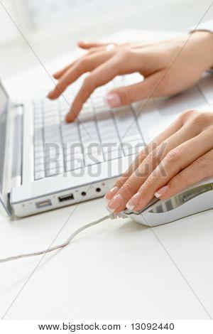 Closeup imagen de mujeres manos usando el ratón y el ordenador portátil.
