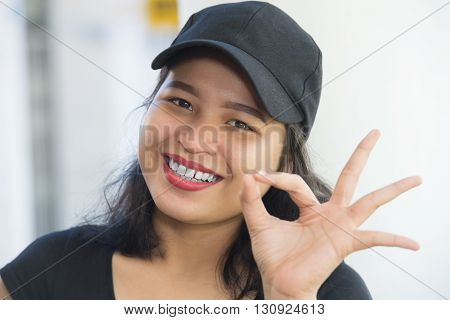 Pretty Asian girl showing OK gesture and smiling