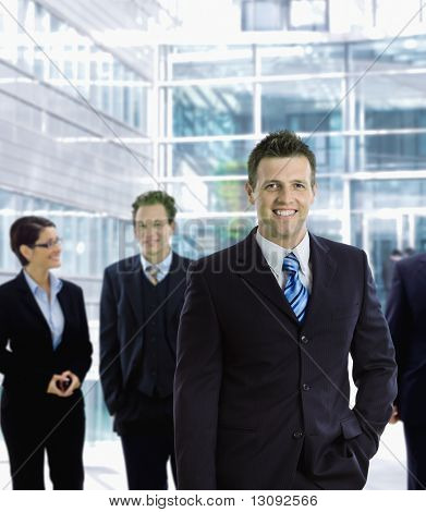 Happy businessman standing in front of other businesspeople, out of office building, smiling.