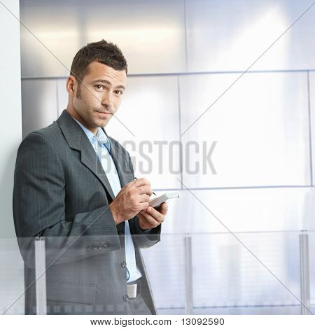 Serious businessman standing in modern office with glass and metal walls, using smart phone.
