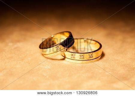 Two wedding rings on a yellow background