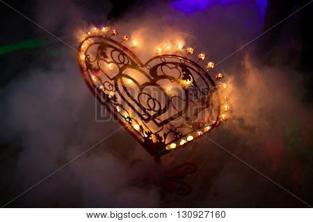 Red metal heart with candles and smoke