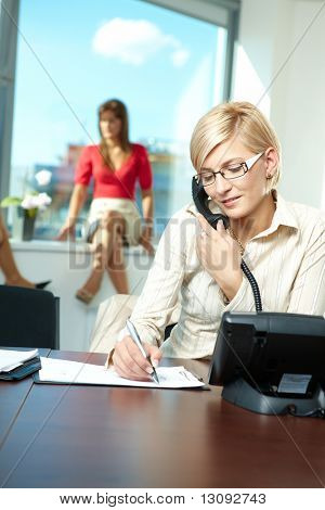 Young businesswoman sitting at desk in office, talking on landline phone, writing notes to personal organizer.