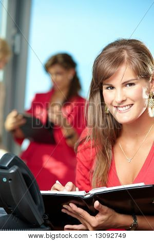 Closeup portrait of young businesswoman writing notes into personal organizer, smiling.