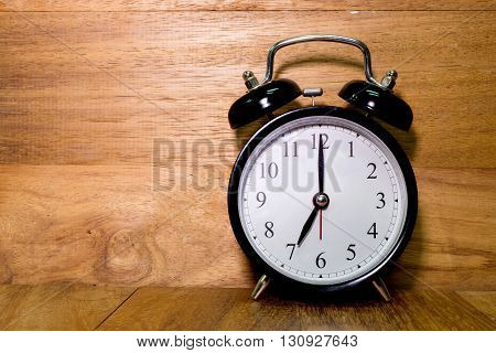 Vintage background with retro alarm clock on wood background Alarm clock shows Seven o`clock