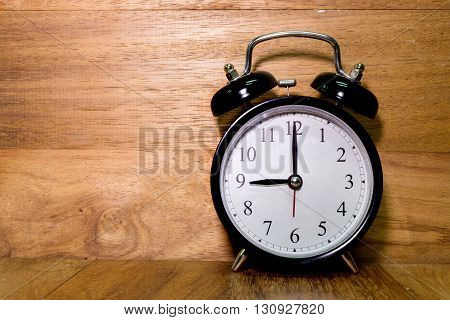 Vintage background with retro alarm clock on wood background Alarm clock shows Nine o`clock