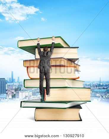 Businessman hanging on top of stack books city background.