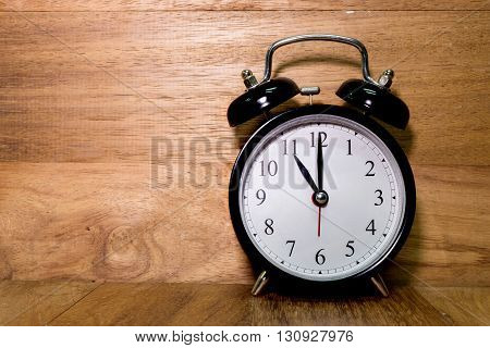 Vintage background with retro alarm clock on wood background Alarm clock shows Eleven o`clock