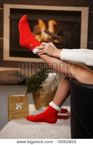 Weibliche Beine an den Weihnachtsmann Socken zu Weihnachten vor Kamin. Geschenke auf dem Boden.