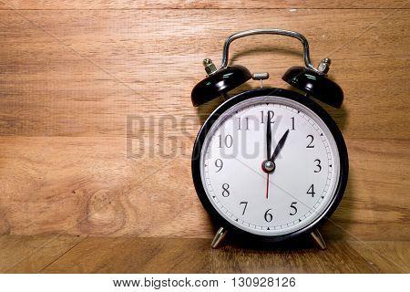 Vintage background with retro alarm clock on wood background Alarm clock shows One o`clock
