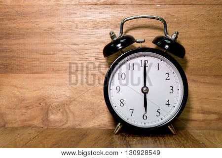 Vintage background with retro alarm clock on wood background Alarm clock shows six o`clock