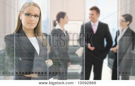 Confident young businesswoman standing in office behind glass wall, businesspeople talking in background.