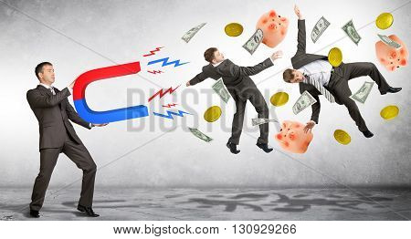 Businessman in suit holding big magnet attracting people and money