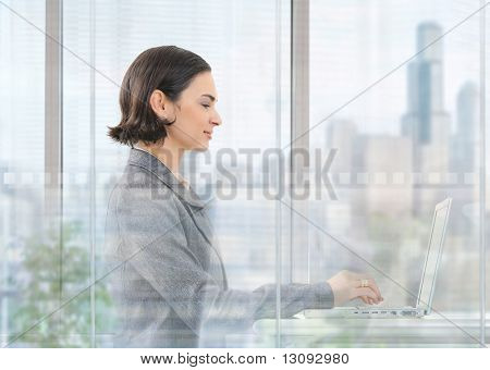Young businesswoman sitting at desk in modern office behind glass wall, using laptop computer, smiling.