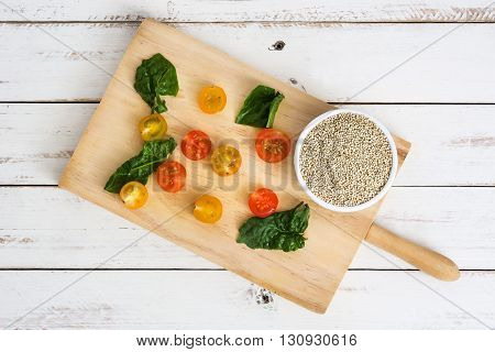 Quinoa, tomatoes and spinach on white wood