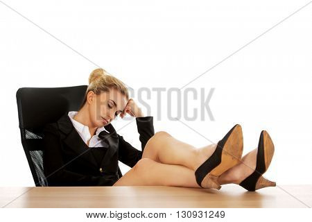 Tired young businesswoman holding legs on the desk