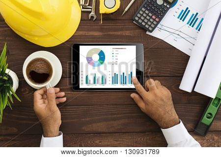 engineer using tablet checking business graph on work table