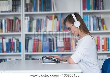 female student study in school library, using tablet and searching for informationâ??s on internet. Listening music and lessons on white headphones