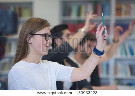 group of  smart students raise hands up in school  classroom on class