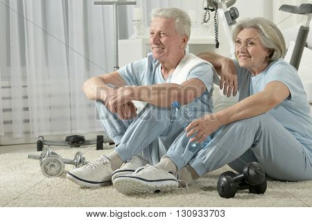 Happy sporty senior couple resting after work out