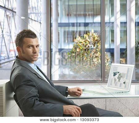 Serious businessman sitting at desk in office, working with laptop computer, looking back.