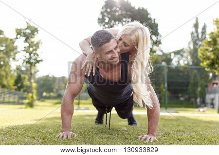 Fit man doing push-ups with woman on back in nature kissing him