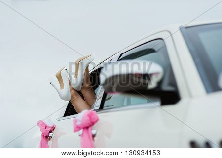 bride's leg in white wedding shoes in the white car window