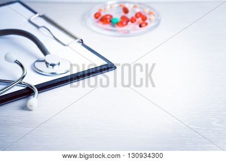 Medical medicine stethoscope and pills on background. Health care or illness. Tablet or drug in hospital or pharmacy. Cardiology heart treatment. Medication prescription