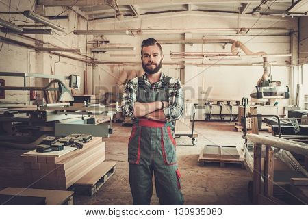 Carpenter doing his job in carpentry workshop.