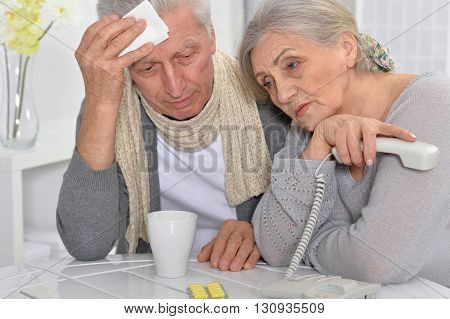 ill Senior man and caring wife calling phone