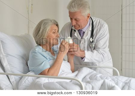 Senior woman in hospital with caring doctor