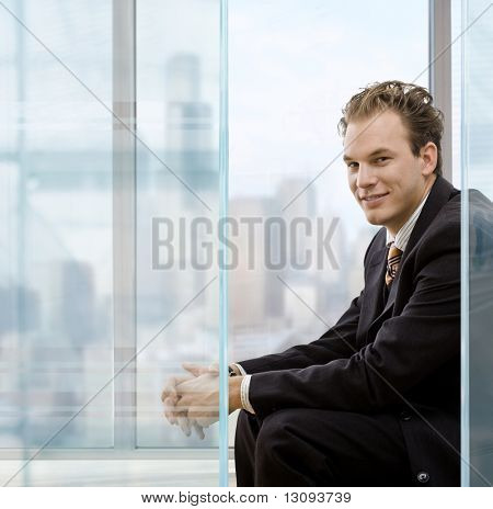 Profile portrait of businessman talking sitting in modrn office in front of windows, smiling.