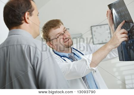 Medical office - middle-aged male doctor explaining computer tomograph scan to patient.
