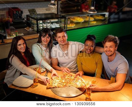 Cheerful multiracial friends having fun eating pizza in pizzeria.