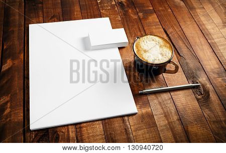 Photo of blank stationery set. Corporate identity template on vintage wooden table background. Letterhead business cards coffee cup and pen. Top view.