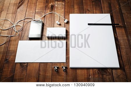 Blank corporate identity template on wood table background. Photo of blank stationery set. Mockup for design presentations and portfolios. Letterhead business cards envelope phone headphones and pencil.