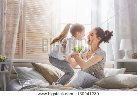 Happy loving family. Mother and her daughter child girl playing and hugging.