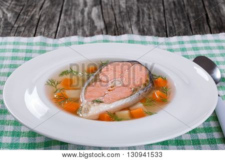 salmon soup with vegetables and dill in a white wide rim dish on a table cloth on an old rustic tableview from above close-up