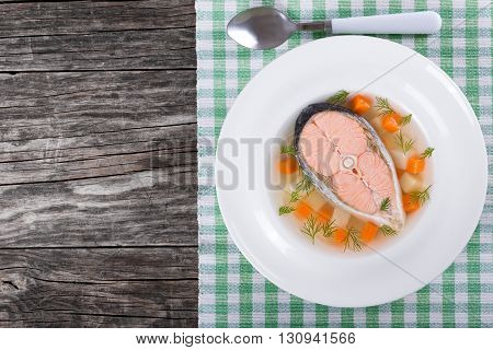 salmon soup with vegetables and dill in a white wide rim dish on a table cloth on an old rustic tableview from above