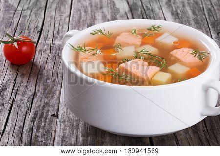 Hearty salmon soup on a white bowl ont a rustic wooden table close-up