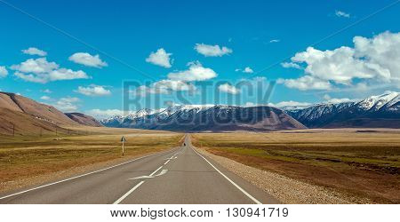 Straight road goes to horizon on mountains backdrop. Altay mountains Siberia Russia.